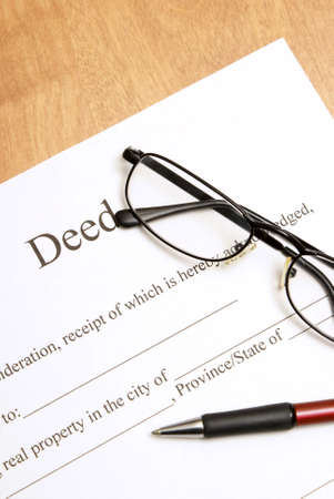 A closeup shot of deed papers and glasses to read the fine print.