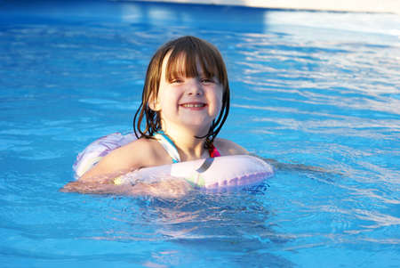 cute little girl smiling: A happy five year old girl enjoys her summertime in the pool. Stock Photo