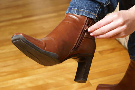 A woman is zipping her fashionable brown boots.