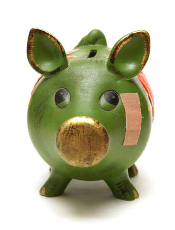 budget crisis: A pig bank and bandage represent financial concepts.
