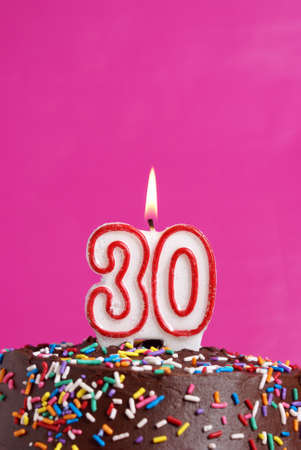 A number candle is lit in celebration of thirty years. Stock Photo - 23132091