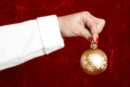 decorate: A woman prepares to decorate using a golden bauble.