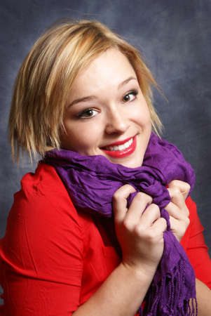 A young woman scrunches her scarf in a warm fashionable pose. photo