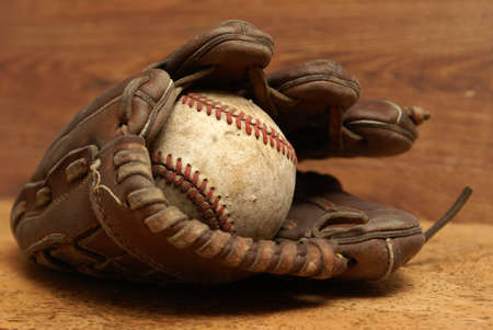 An old baseball inside a well used glove. photo