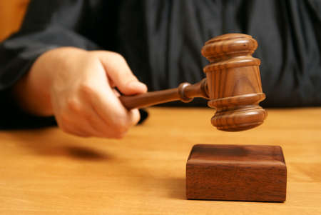 A professional judge declares the legal proceeding with a final hit using the gavel. Stock Photo