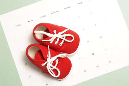 A pair of baby shoes on a monthly calendar to represent many parenting concepts. Standard-Bild