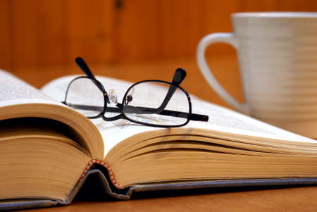 business book: A macro shot of an open book with reading glasses and a cup of coffee.