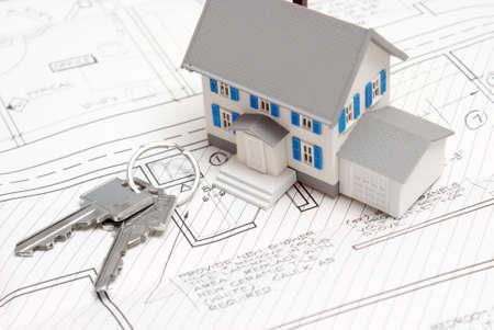 Een model huis rust op blauwdrukken met sleutels van de nieuwe woning.