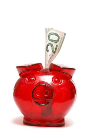 A red piggy bank with a twenty dollar bill for the money saving mind set. 版權商用圖片
