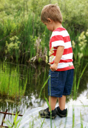 culvert: A happy two year old boy sparks curiousity at a nearby culvert while searching for tadpoles, frogs, and fish. Stock Photo
