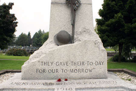 A world war memorial made of stone, stands proudly in the park of Smiths Falls, Ontario.