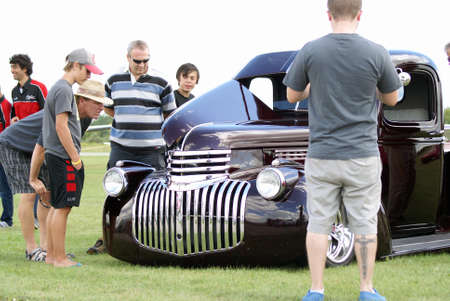 SMITHS FALLS, ON, CANADA - AUGUST 23, 2014.  A crowd gathers around a sport car on display at the third annual Race the Runway event held at the Russ Beach Airport, in Smiths Falls, Ontario, Canada, on August 23, 2014.