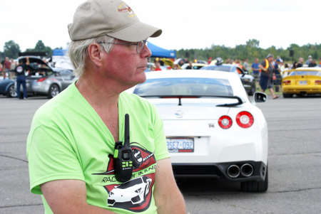 patrolling: SMITHS FALLS, ON, CANADA - AUGUST 23, 2014.  A staff member patrolling the third annual Race the Runway event held at the Russ Beach Airport, in Smiths Falls, Ontario, Canada, on August 23, 2014.