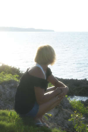 ocean state: A woman sits on a hill while overlooking the ocean in a dreamy state of mind.