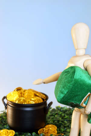 A wooden mannequin directs the viewer to a pot of gold. photo