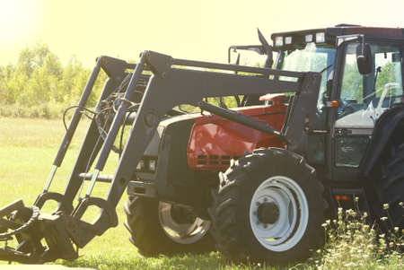 A farmers tractor awaits in the pasture for the next days work as the sun sets in the western sky. photo
