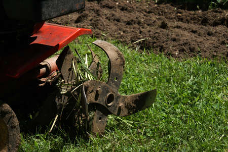 plough machine: A closeup shot of a rototiller machine working the fields in the countryside. Stock Photo