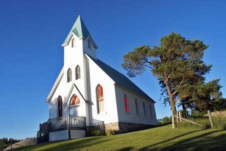 Een mooie samenstelling van een witte kerk in het charmante platteland. Stockfoto