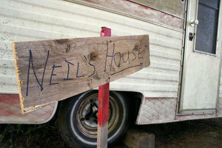 uneducated: A closeup on a sign outside of an old beatup trailer. Stock Photo