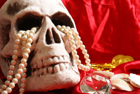 cursed: A spooky skull thats holding on to some treasure. Stock Photo