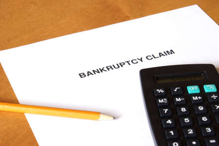 creditors: A bankruptcy claim form with a calculator and pencil. Stock Photo