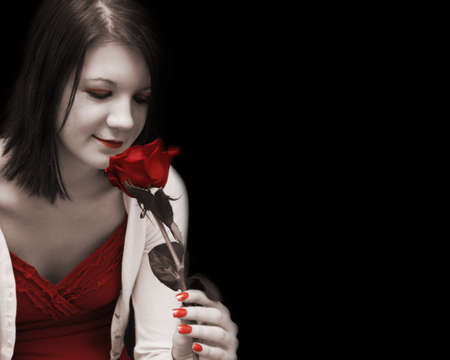 coloring lips: A beautiful woman dreams passionately as she glances at her red rose in this artisticly toned image. Stock Photo
