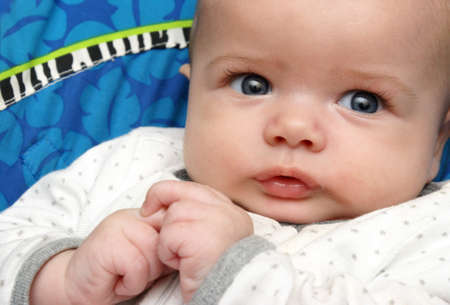 awake: A closeup view of a handsome baby boy resting casually and fully alert. Stock Photo