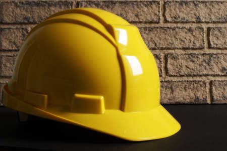 A yellow hardhat rests on a construction site.