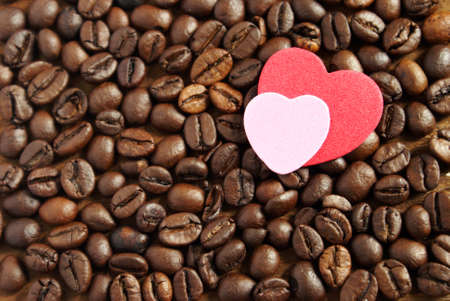 grasp: A simple grasp on the everyday coffee lover concept using gourmet coffee beans and a couple heart shape cutouts.