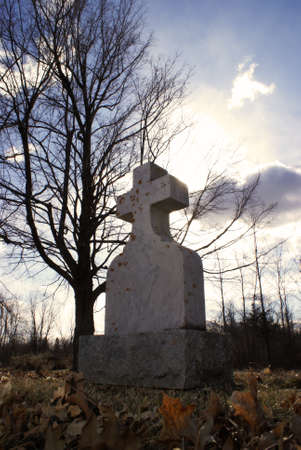 stone tombstone: An old tombstone in a quiet gravesite with the sunshine backlighting the cross in a spirtual manner.