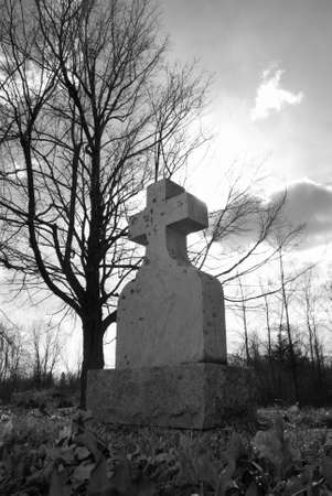 spirtual: An old tombstone in a quiet gravesite with the sunshine backlighting the cross in a spirtual manner.