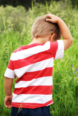 boyhood: A young boy explores the great outdoors while creating some thoughts in this candid image of him scratching his head during his boyhood sense of wonder. Stock Photo