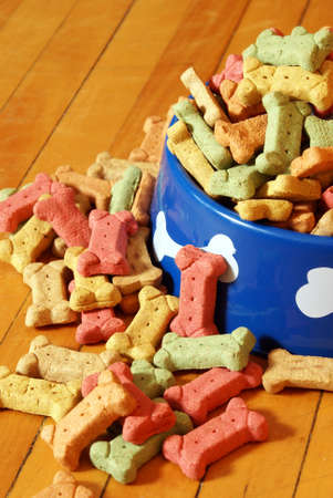 abundant: An over abundant supply of various dog treats flowing from a dish.