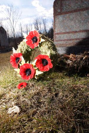 그 타락한 사랑하는 사람의 영광스러운 기억을위한 묘비에 양 귀 비 화 환보기 닫기를. 스톡 콘텐츠