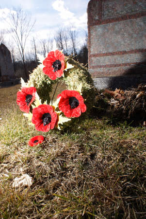 those: A close view of a poppy wreath at a tombstone for the honorable remembrance of those fallen loved ones.