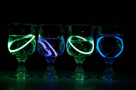 alcoholic drink: Four neon glowing party drinks illuminated in the nightclub.
