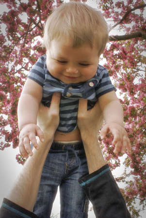 arms up: A father throws his infant son in the air to get a happy reaction from his enjoyment.