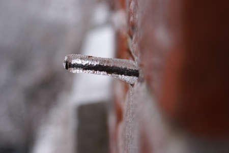 An abstract image of a winter iced construction nail in a brick wall.