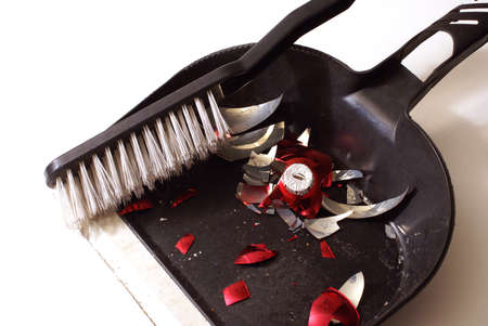 smashed: A smashed red holiday bauble has fallen to many pieces so a broom and dustpan come to clean up the mess. Stock Photo