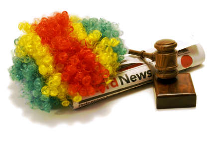 An isolated clowns wig, newspaper, and gavel to illustrate how clowns have been an issue across the nation this year.