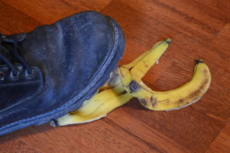 A man is about to have an accident with a banana peel in the workplace. Фото со стока