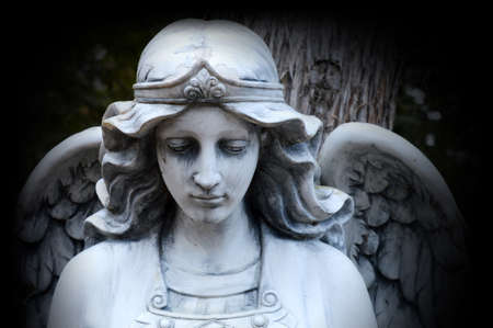 A beautiful Angel watching over Gods creation set in a stone statue. Stock Photo