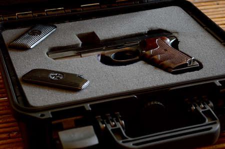 A handgun is presented from the inside of a lock box. Standard-Bild