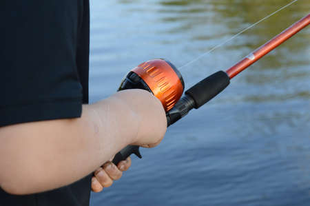 Closeup of a young boy fishing with his rod and reel. 版權商用圖片