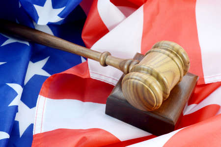 A wooden gavel and American flag come together for representing the United States legal system.