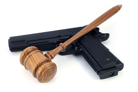 An isolated handgun and wooden gavel over a white background for the concept of gun laws and legalities. Banque d'images - 128903486