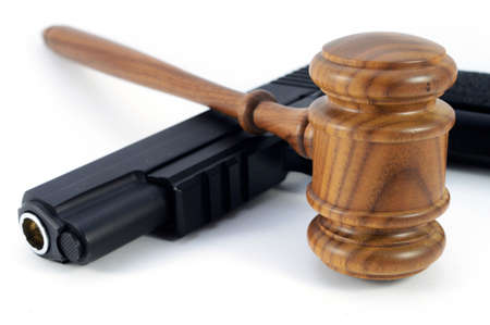 A handgun and wooden gavel used over a white background to conceptualize gun laws and legalitites. Banque d'images - 128903520