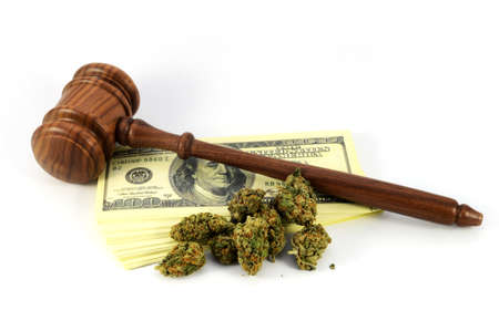 A concept of the revenue made from legalized weed with a wooden gavel and marijuana with American bank notes.