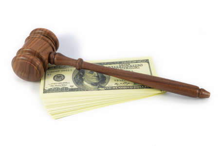 A concept for legal expenses using an isolated wooden gavel ontop of a stack of American bank notes over a white background.