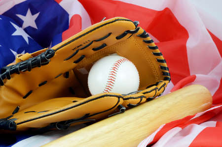 A still-life of a mitt and ball and bat and flag representing the favorite American pastime of Baseball.